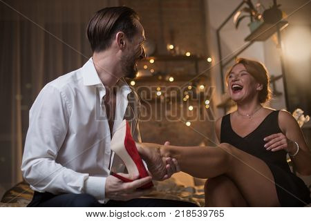 Joyful lovers are sitting on bed after romantic date. Man is taking off female shoe before making a foot massage. Woman is looking at him and laughing