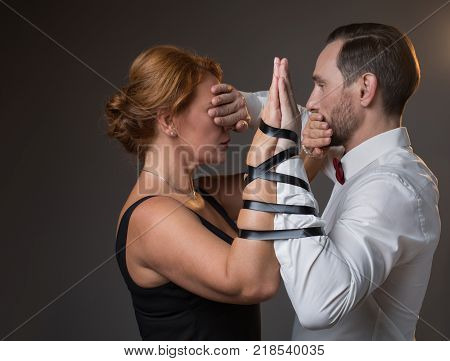 Eternal promise. Side view profile of middle-aged married couple standing while having their arms bound by ribbon. Man is closing female eyes while woman covering male mouth. Isolated