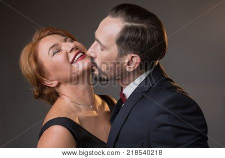 Affectionate middle-aged man is kissing female neck with passion. Woman is raising head up and laughing. Intimacy concept. Isolated