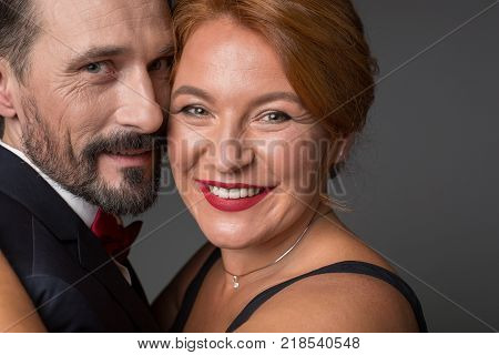 Portrait of happy middle-aged man and woman cuddling and smiling. They are standing in formalwear. Isolated