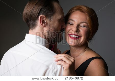 Always happy with you. Portrait of cheerful adult lady enjoying passionate hug of her male lover while he is whispering desire into her ear. She is smiling with closed eyes. Isolated poster