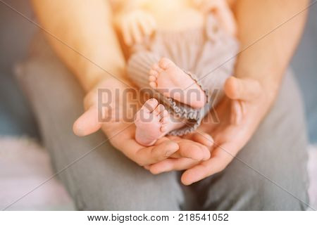 Hand of a young father touch his newborn baby foot 2 week old . Concept photo of newborn, baby, mother, motherhood, parenting and lifestyle