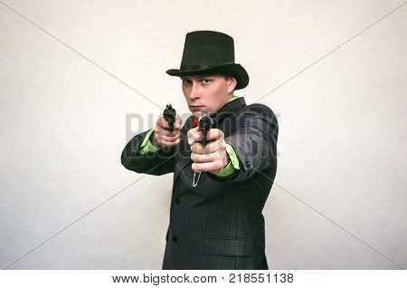 The spy. Secret service. Serious nad confident detecive agent holds pistol gun in his hands and aiming in the screen. Retro gangster isolated on white background.