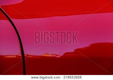 Reflections in side wing of red sport car