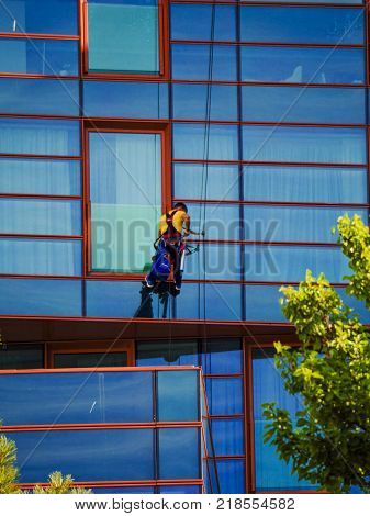 Window washer cleaning the windows of the modern high-rise building.