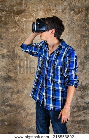 Young Man in Virtual Reality Glasses by the Old Wall in the Derelict House