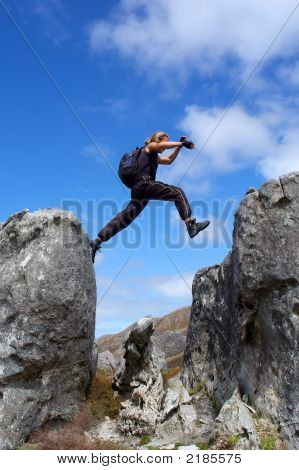 Man With Long Hair Jumps From Rock