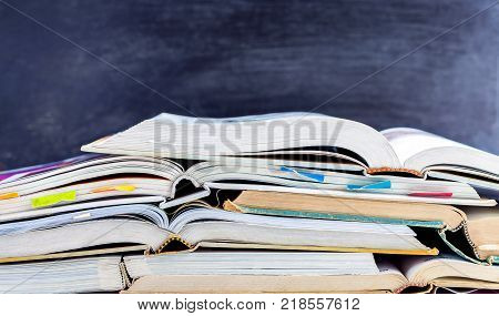 Open hardback and textbook stacked on the table on blackboard background. The concept of intelligence comes from education. focused on the textbook.