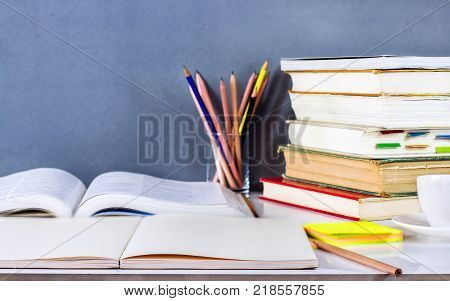 Open textbook and hardback stacked with pencils on the table. The concept of intelligence comes from education. focused on the textbook.