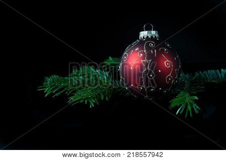 Low key view of Christmas bulb and a twig of Chritmas tree.
