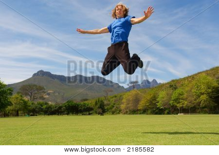 Young Man Jumps Above Misty Majestic Mountains