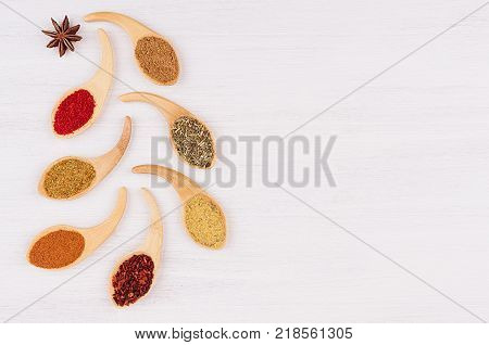 Multicolored asian spices in quaint spoons on white wooden background as decorative christmas tree. Top view.