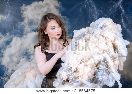 asian woman holding cloud in her hands and studing the motherboard silhouette pattern on the cloud. technology management concept.