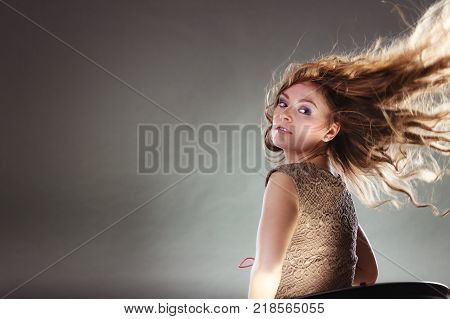 Mysterious enigmatic woman in studio on grey. Young intriguing attractive girl with flying long curly hair in motion. Shining light.
