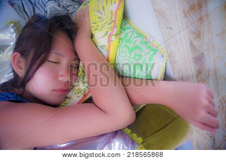 close up face portrait of young and beautiful Asian Chinese girl sleeping peacefully and tranquil taking a nap resting tired and exhausted lying on colorful pillow and cushion