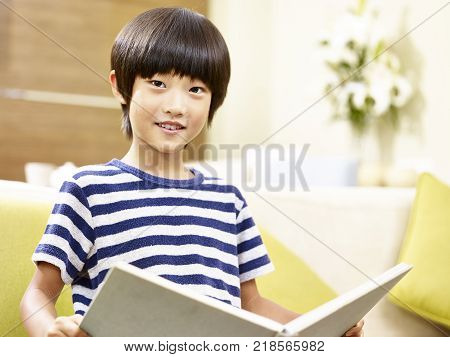 7 year-old asian little boy sitting on couch holding a book looking at camera smiling.