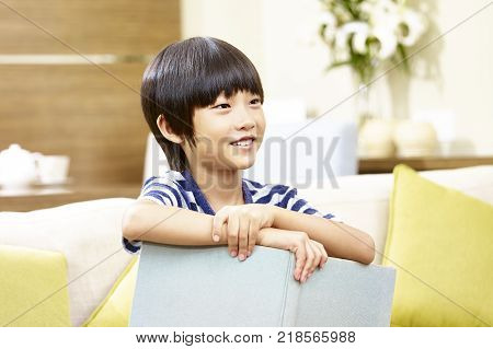 7 year-old asian little boy sitting on sofa holding a book smiling.