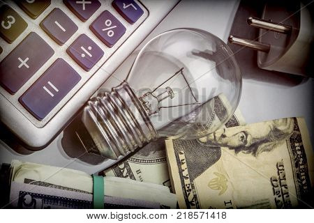 Calculator and money next to a light bulb, the concept of energy saving