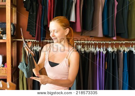 Red young beautiful woman shopping in clothing store