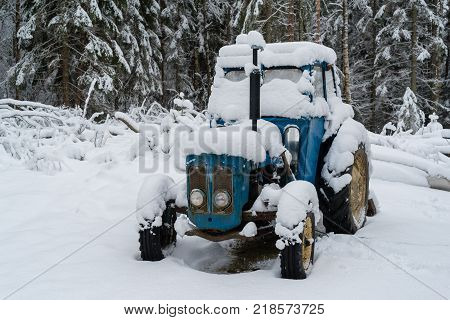 A blue tractor covered in white snow