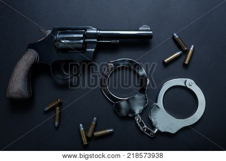 Gun with ammunition and shackle on black background Top view