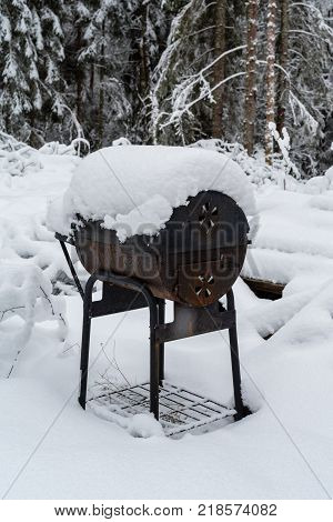 An old bbq grill covered in white snow