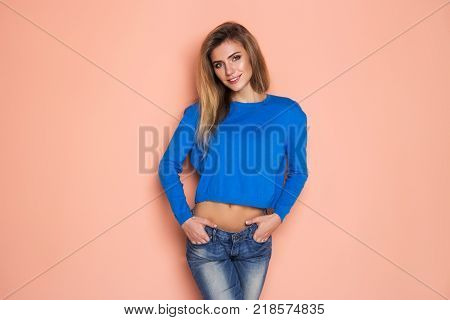 Portrait of a sexy cute woman wearing in blue blouse posing isolated on a orange background.