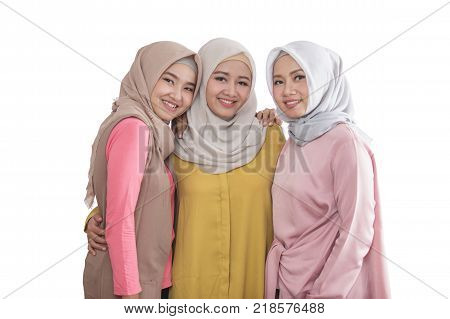 portrait of three beautiful siblings smiling on the camera isolated on white background