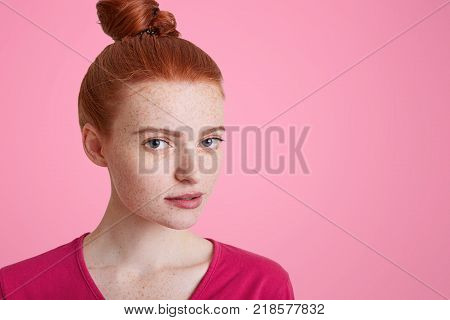Close Up Portrait Of Freckled Young Female Wears Casual Pink Sweater, Looks Confidently At Camera, D