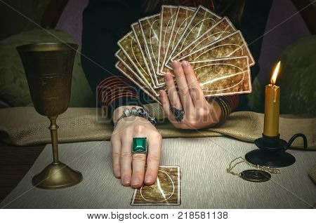 Tarot cards on fortune teller desk table. Future reading. Woman fortune teller holding and hands a deck of tarot cards.