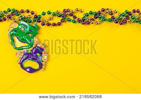 Mardi gras carnival background - beads and mask on yellow background