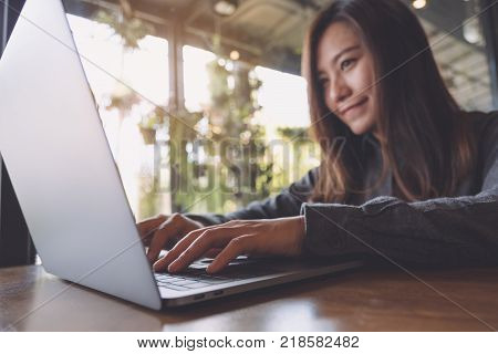 Closeup image of a beautiful Asian business woman looking working and typing on laptop keyboard in office