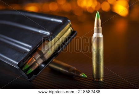 Ammo that fits in an AR 15 and magazine with orange background