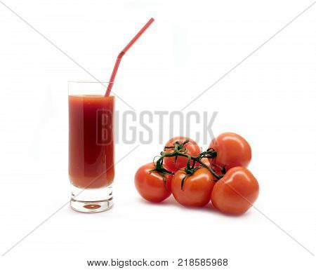 A glass with tomato juice with drinking straw and three ripe tomatoes studio shot isolated on white background