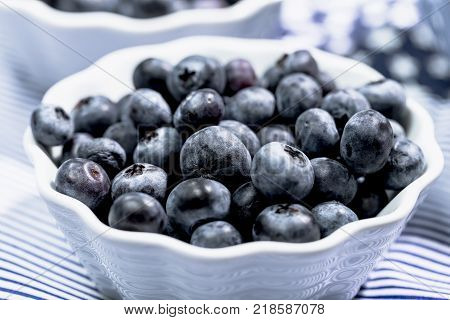 Blueberries in small white bowl on light blue background