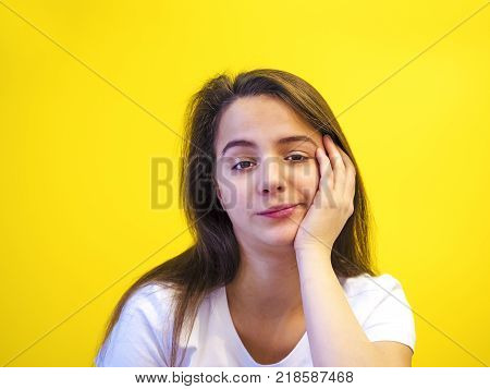 I dont know. Headshot of a dubious, uncertain or skeptical young Caucasian woman in a white T-shirt expressing uncertainty, doubt, ignorance or indifference, creating studio-insulated studios