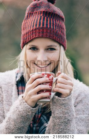 Woman drinking hot drink. Girl with red nails holding a hot cup of coffee or tea outdoors.