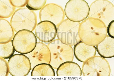 Backlit lemon and lime slices. Abstract exotic background, closeup texture of cut tropical fuits. Healthy eating, vitamins and veggie concept, top view