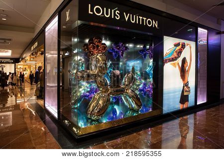 Paris France - October 30 2017: Showcase of famous designer bag brand Louis Vuitton in Galeries Lafayette shopping centre in Paris. Festive christmas decorations are made by an artist Jeff Koons.