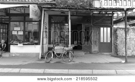 NOVI PAZAR, SERBIA - JULY 25, 2017: black-white view commercial street of working class: and old bycicle is parking in front of an anonymous tavern next to a shoe store