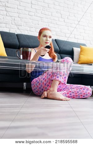 Girl with beauty mask watching televison at home. Young woman reading magazine and relaxing in living room. Female beauty, skin and body care, lotion and cream. People and lifestyle