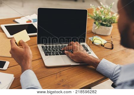 Unrecognizable man shopping online with credit card and laptop, sitting at office, e-commerce concept, copy space