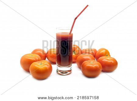 A glass with tomato juice with drinking straw and many scattered ripe tomatoes studio shot isolated on white background