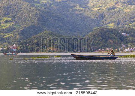 POKHARA NEPAL - September 29 2013: Resident on old small boat sailing on the Phewa lake. Rowboat symbol of Phewa lakeside in Pokhara city.
