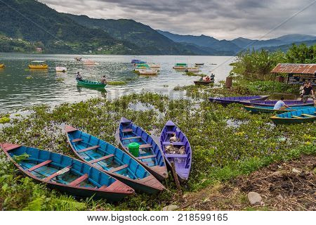 POKHARA NEPAL - September 29 2013: Residents on old small boats sailing on the Phewa lake. Rowboat symbol of Phewa lakeside in Pokhara city.