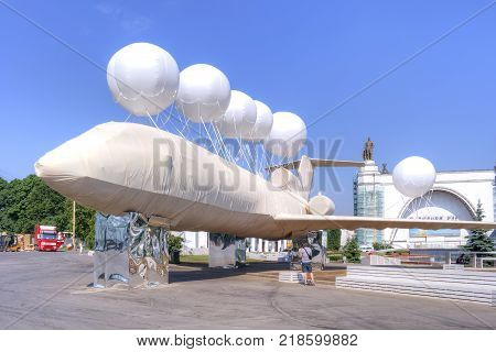 MOSCOW RUSSIA - May 28.2014: Exhibition of Achievements of the People's Economy (VDNKh). Artistic installation bandaged airplane with balloons on a background exhibition pavilions