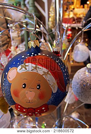 Closeup of a painted Christmas glass bauble a lovely teddy bear hanging on a christmas market
