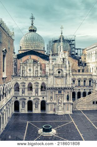 Courtyard of Doge`s Palace or Palazzo Ducale in Venice, Italy. Doge`s Palace is one of the main tourist destination in Venice. Domes of Saint Mark`s Basilica in the background.