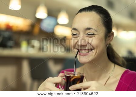 Beautiful smiling girl in red dress drinks mulled wine at coffee shop. toned