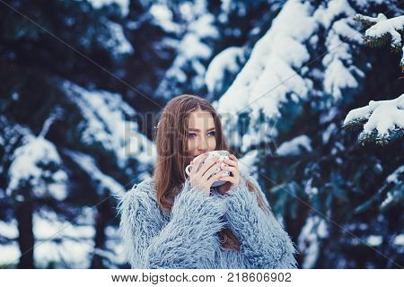 Young woman in a coat is drinking tea in the forest